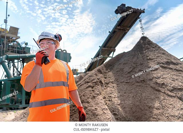 Worker talking on walkie talkie with crusher and concrete screening machine in concrete recycling site