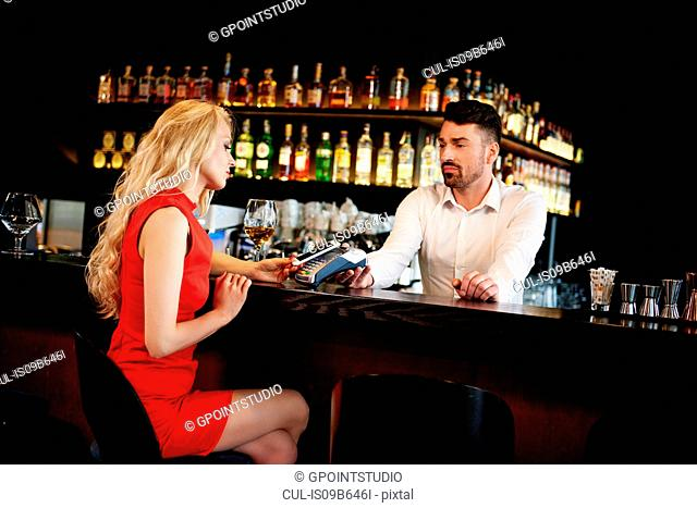 Young woman making smartphone payment sitting at bar