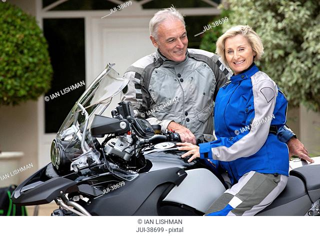 Portrait of smiling senior woman on motorcycle in driveway