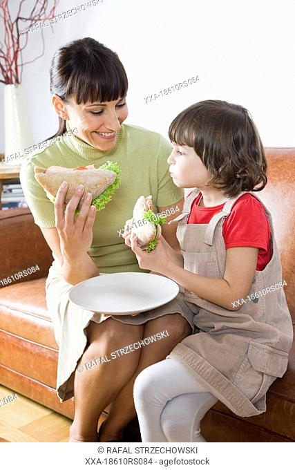mother and daughter eating sandwiches