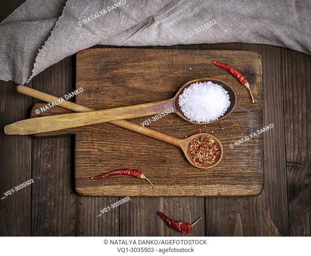 wooden spoon with white large salt and spices on a cutting board, top view