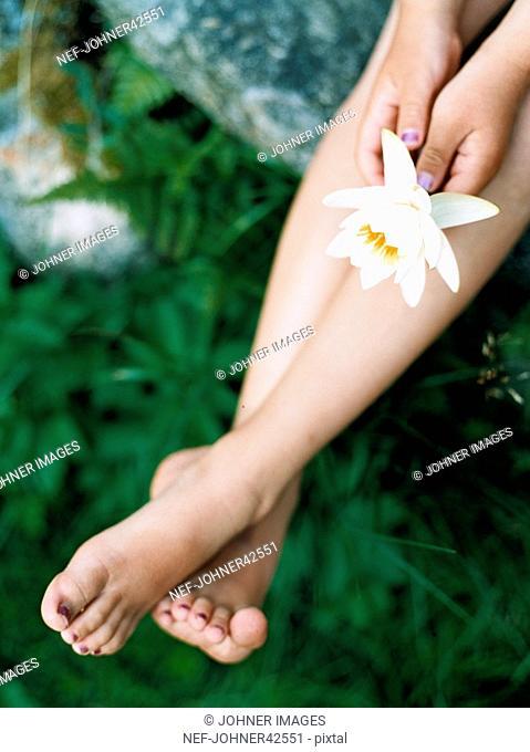 Child's hands holding lotus flower
