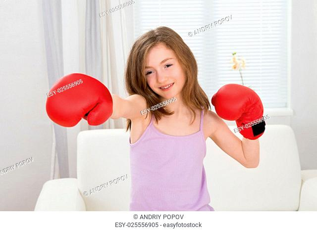 Cute Girl Punching With Boxing Gloves In Living Room