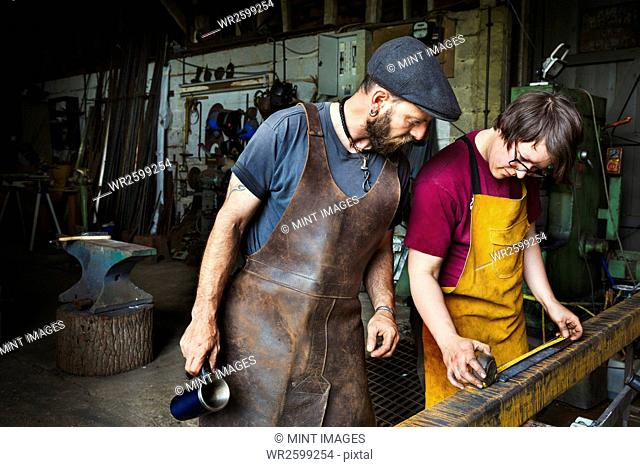 Two blacksmiths measure a length of metal in a workshop