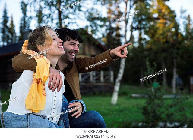 Happy couple sitting on bench, man pointing at distance