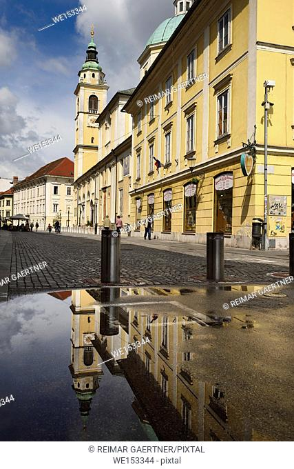 Clock and Bell tower of St. Nicholas Catholic church Ljubljana Cathedral reflected in a puddle on Cyril Methodius Square Ljubljana Slovenia