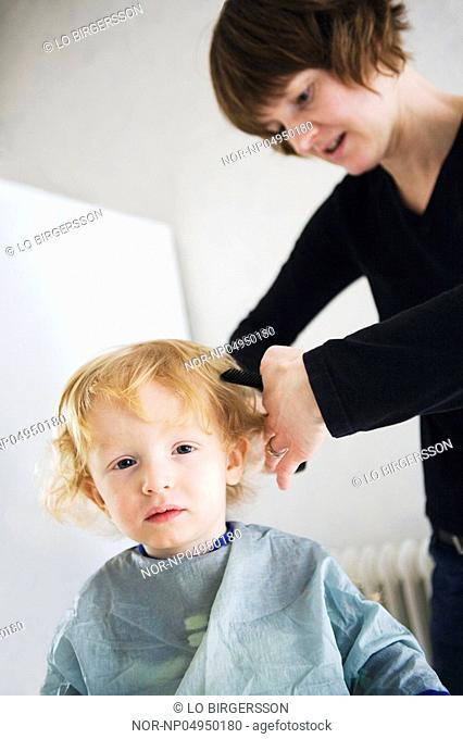 A hairdresser cutting the hair of a child, Sweden
