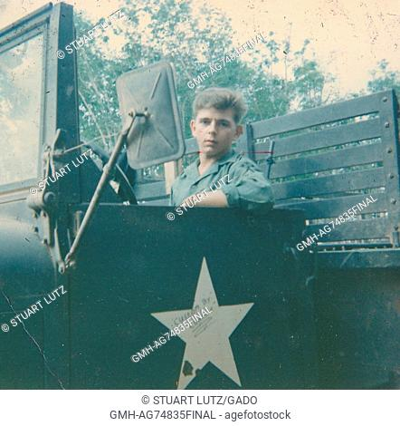 United States Army Serviceman sitting in the open cab of a large truck, bullet holes can be seen in the white star on the door