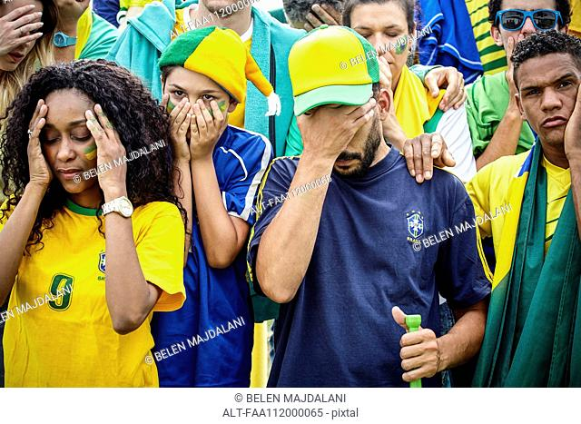 Brazilian football fans looking disappointed at match
