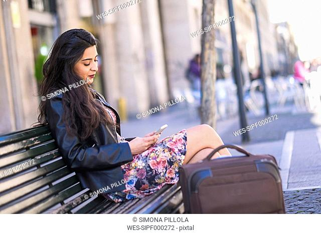 Young woman with baggage sitting on a bench looking at her smartphone