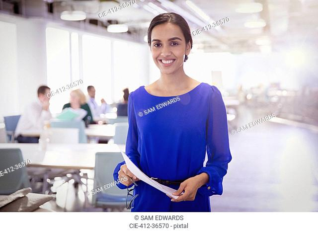 Portrait smiling businesswoman with paperwork in office