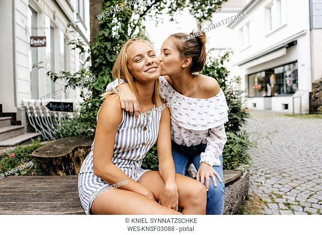 Young woman kissing female friend in the city