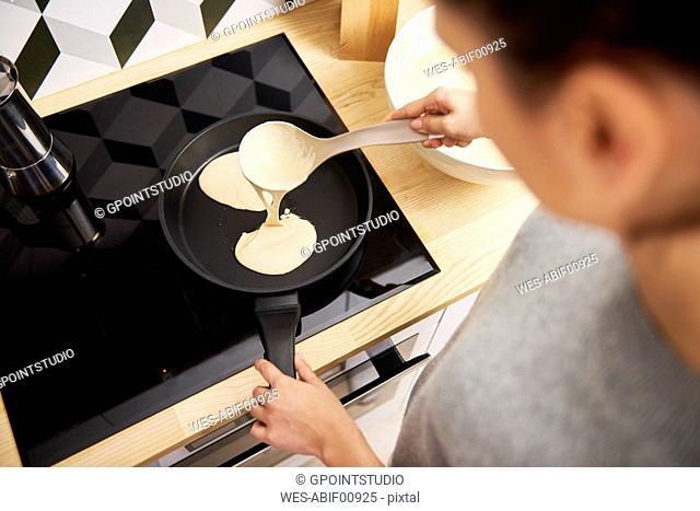Young woman preparing pancakes