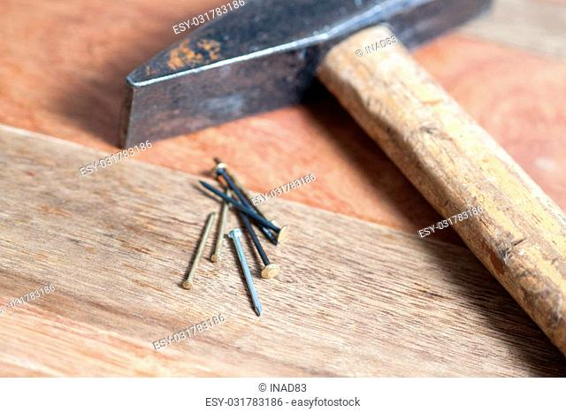 hammer with nails on wooden background