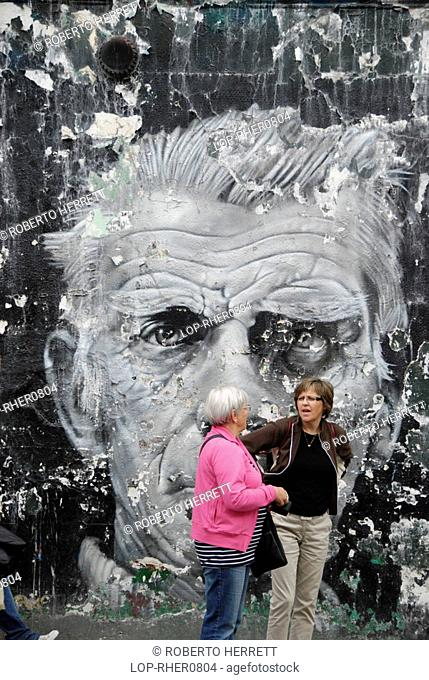 England, London, Notting Hill, Two tourists standing in front of a large mural of Samuel Beckett in Blenheim Crescent near Portobello Road