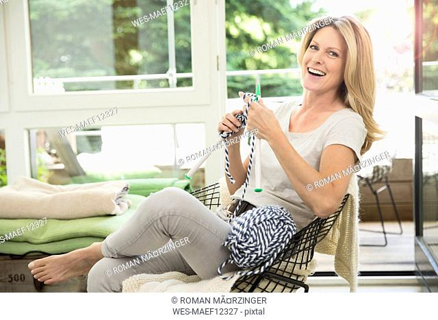 Mature woman sitting in living room, knitting