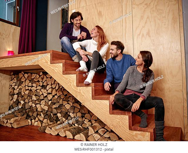 Friends sitting on wooden stairs having fun