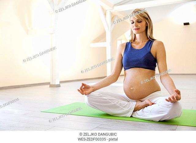 Prenatal yoga, woman meditating, lotus asana