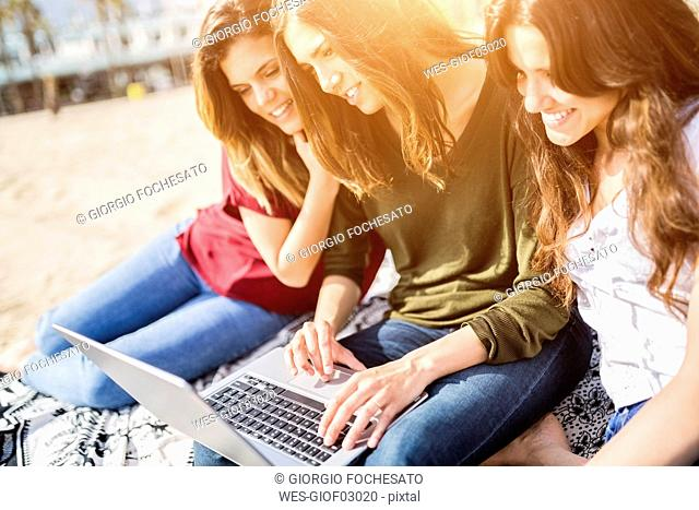 Three happy female friends using a laptop on the beach