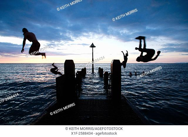 Aberystwyth Wales Uk, Wednesday 16 September 2015. . UK Weather : Students enjoying themselves in silhouette diving and swimming off the seaside jetty after...