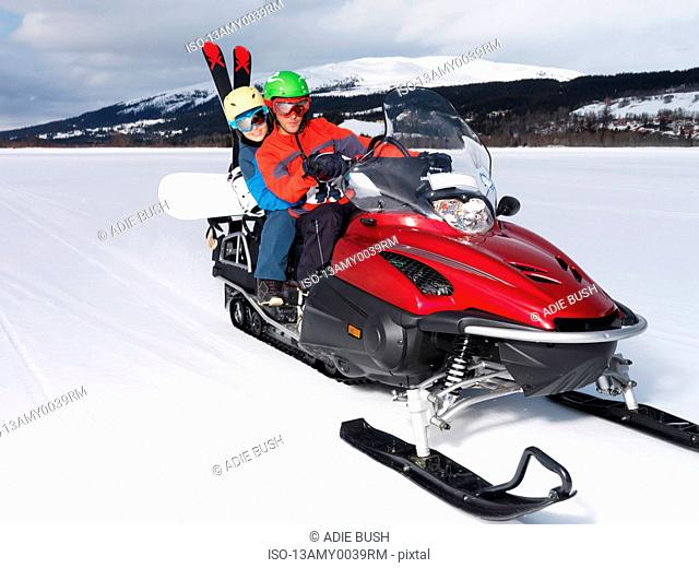 A couple riding a red skidoo