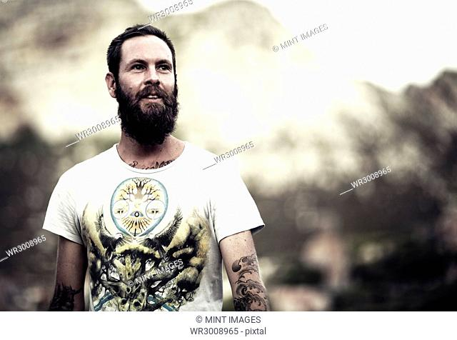 Portrait of bearded man wearing printed T-Shirt, tattoos on arms and chest, mountains in the background