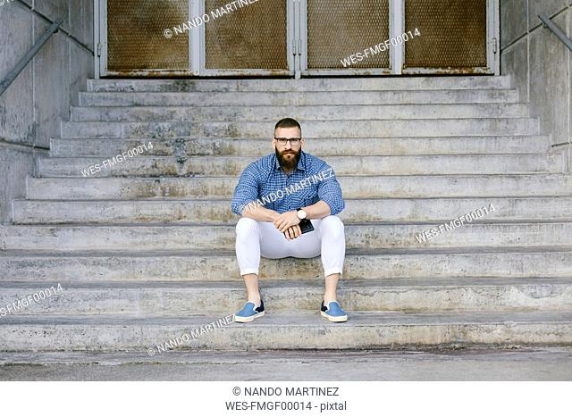 Portrait of bearded hipster businessman with smartphone sitting on stairs