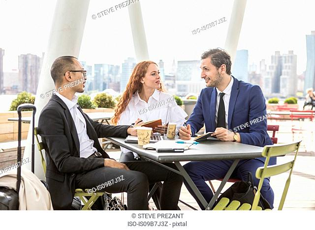 Businessmen and woman meeting at waterfront cafe with New York skyline, USA