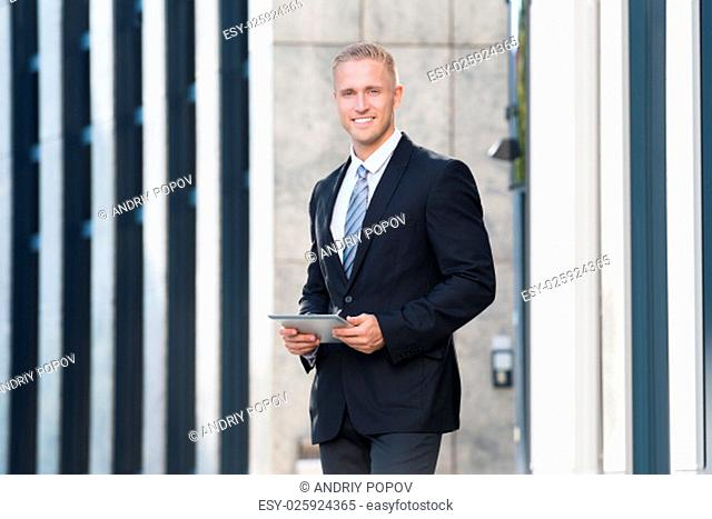 Portrait Of A Young Businessman Looking At Digital Tablet