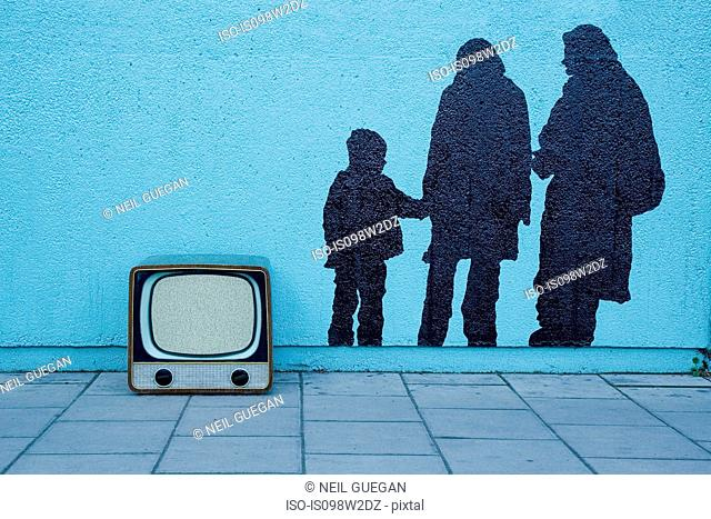 Retro television by blue wall with mural of three people