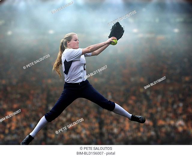 Caucasian softball player pitching ball in stadium