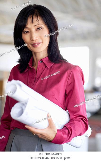 portrait of middle aged woman with blueprints