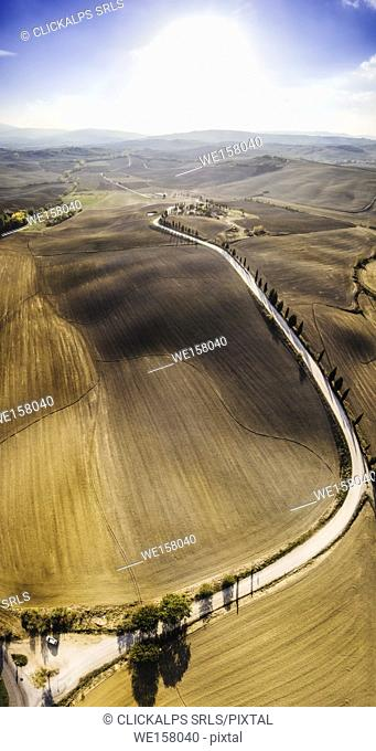 Montichiello, Orcia Valley, Province of Siena, Tuscany, Italy, Europe. Aerial view of the iconic cypresses with road from above