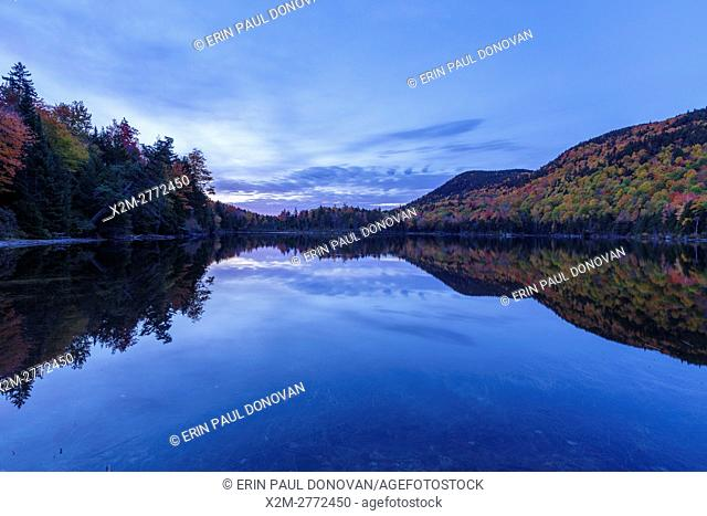 Reflection of autumn foliage in Upper Hall Pond in Sandwich, New Hampshire USA during morning blue hour