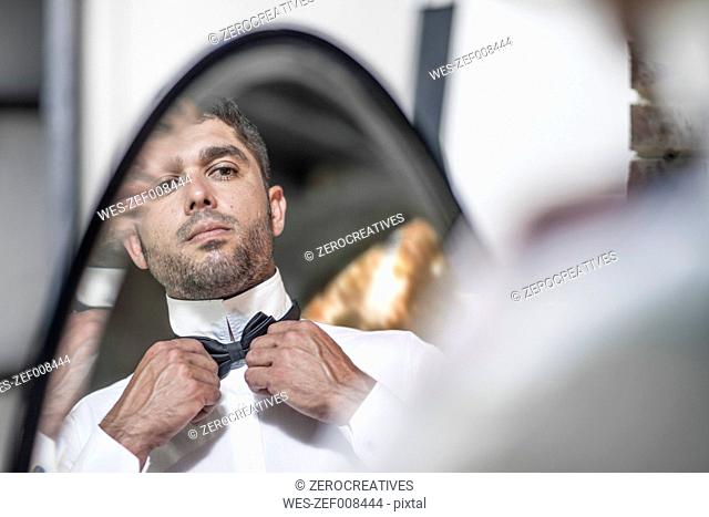 Man looking in mirror adjusting bowtie