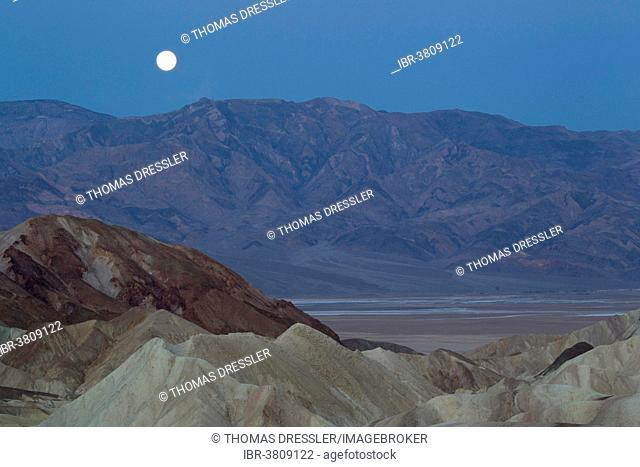 Full moon over the Panamint Range and the Death Valley at dawn, seen from Zabriskie Point, the badlands of Gower Gulch in the foreground