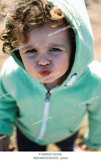 Portrait of little girl wearing hooded jacket pouting mouth