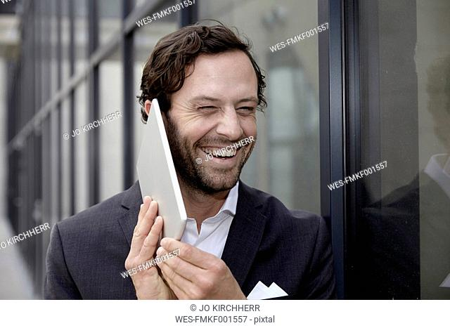 Portrait of laughing businessman trying to phone with his digital tablet
