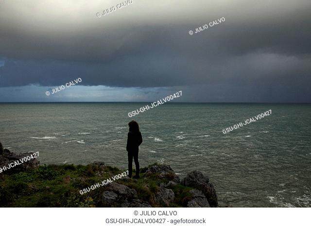Young Man Standing on Rocky Cliff Looking out to Ocean with Stormy Sky, Rear View