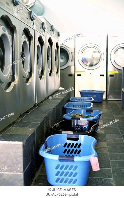 View of a row of washing machines and laundry baskets in a laundromat