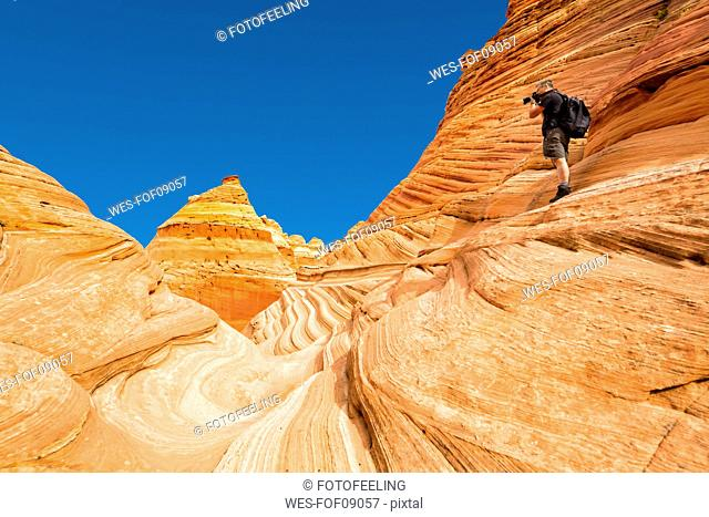 USA, Arizona, Page, Paria Canyon, Vermillion Cliffs Wilderness, Coyote Buttes, red stone pyramids and buttes, man taking picture