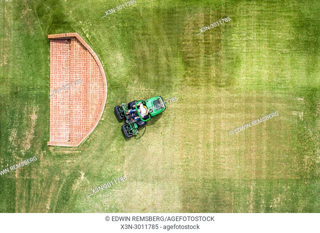 Shot looking directly down at man operating riding lawn mower to cut grass, Tifton, Georgia. USA