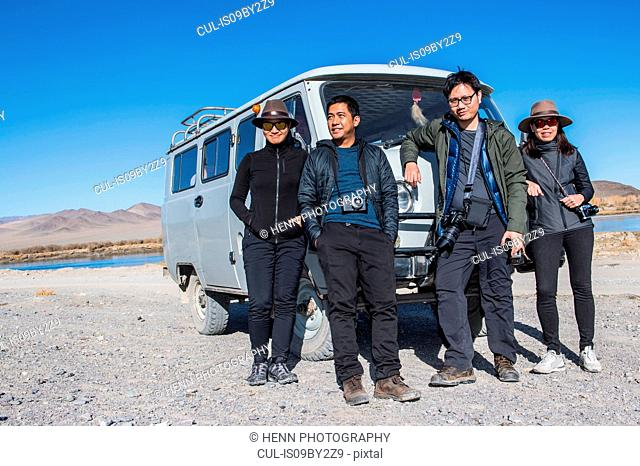 Group of friends posing in front of off road vehicle, Ölgiy, Bayan-Olgiy, Mongolia