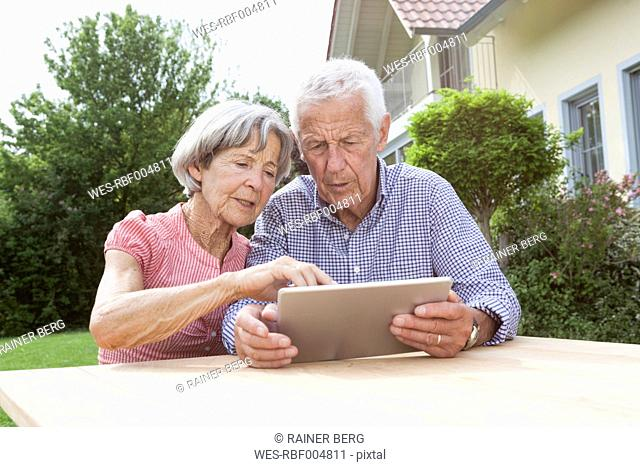 Senior couple using digital tablet in garden