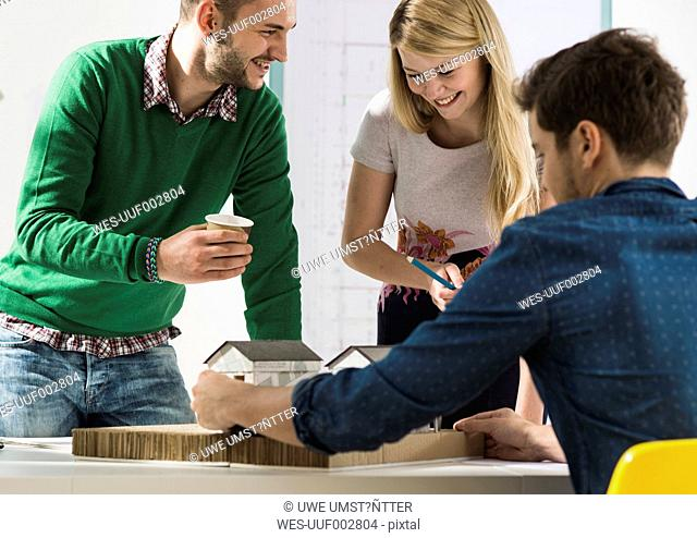 Three smiling young architects in office discussing