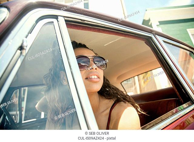 Young woman looking out from vintage car window, Cape Town, South Africa