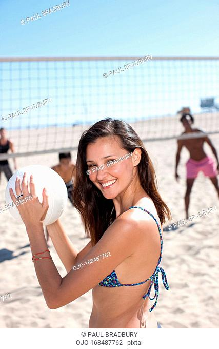 Woman playing beach volleyball with friends