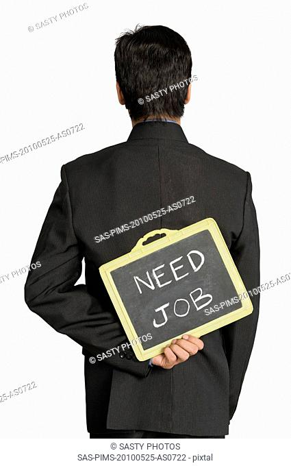 Businessman holding a slate behind his back