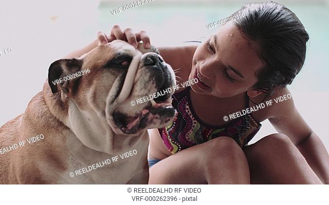 Girl stroking her bulldog near swimming pool