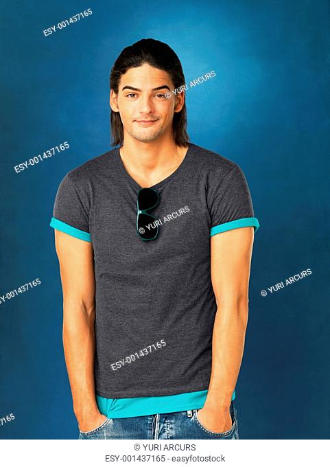 Casual man standing with hands in pockets against blue background